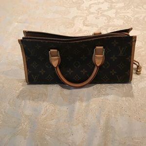 Triangle top handle Louis Vuitton bag.